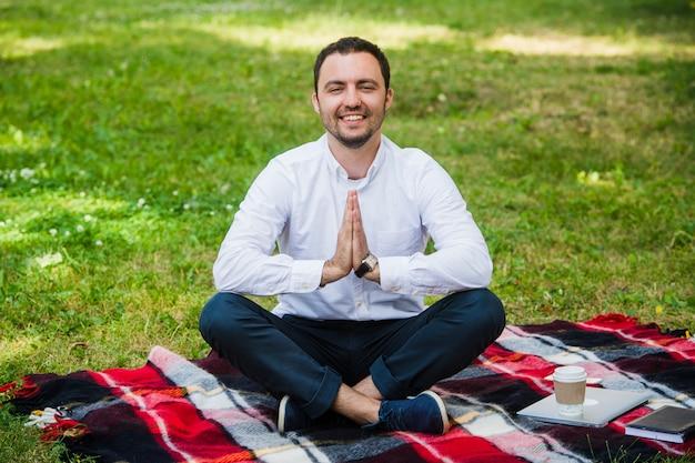 L'uomo d'affari all'aperto fa le palme della tenuta di esercizio di yoga nel gesto e nel sorridere del namaste