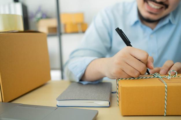 Proprietario dell'uomo d'affari che scrive l'indirizzo del cliente sulla scatola di imballaggio dopo aver confermato l'ordine di acquisto
