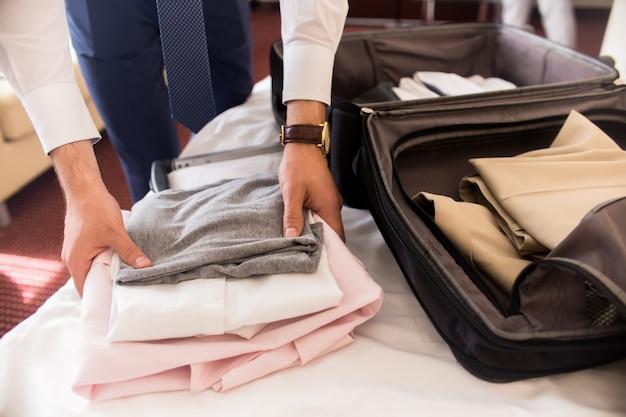 Uomo d'affari packing bags per il viaggio
