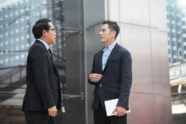 Partner dell'uomo d'affari che si consulta e che discute ad all'aperto