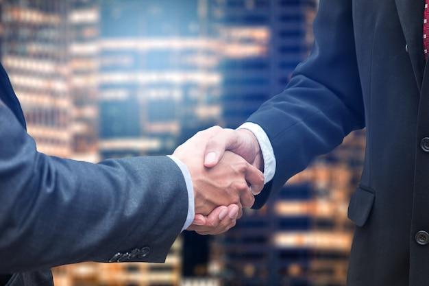 Stretta di mano riunione di partenariato dell'uomo d'affari nell'edificio per uffici della città