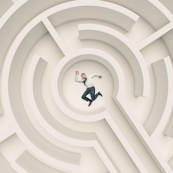 L'uomo d'affari è svenuto a terra nel mezzo di un labirinto. concetto di difficoltà e sfida.