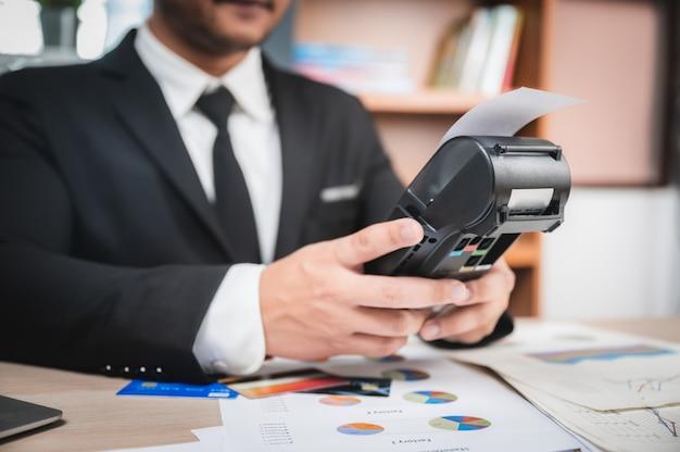 Uomo d'affari che paga dalla carta di credito con una macchina del lettore della carta di credito, l'e-banking e il concetto online di vendita di affari