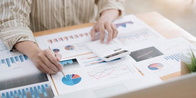 Penna dell'uomo d'affari che indica il fatturato con rapporto grafico e usa il calcolo per i dati di analisi