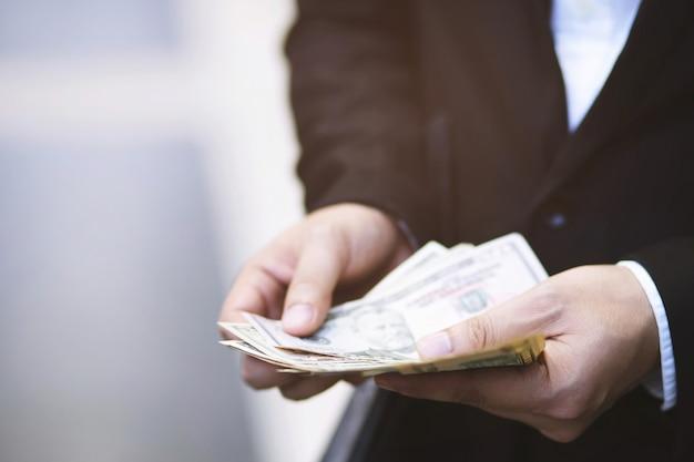 Uomo d'affari la persona che tiene un portafoglio nelle mani di un uomo prende i soldi di tasca. risparmio di denaro.