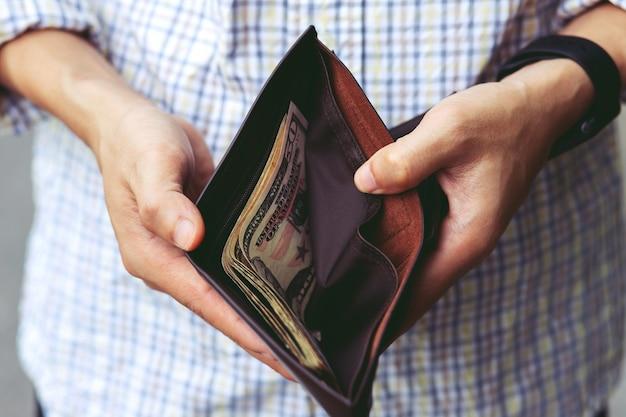 Uomo d'affari la persona che tiene un portafoglio nelle mani di un uomo prende i soldi di tasca.