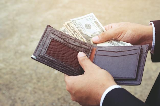 Persona dell'uomo d'affari che tiene un portafoglio nelle mani di un uomo