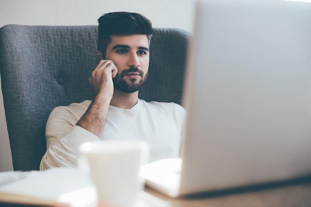 Uomo d'affari al telefono. giovane fiducioso che parla al telefono cellulare e guarda il laptop mentre è seduto al suo posto di lavoro in ufficio