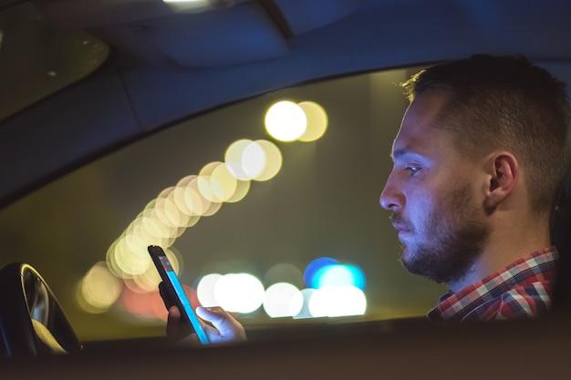 Il telefono dell'uomo d'affari all'interno dell'auto in autostrada. sera notte