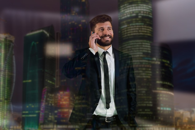Il telefono dell'uomo d'affari vicino alla finestra sullo sfondo di un grattacielo
