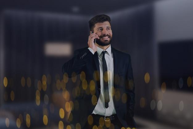 Il telefono dell'uomo d'affari vicino alla finestra con le luci della città