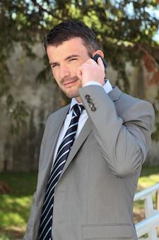 Uomo d'affari al telefono all'aperto in primavera