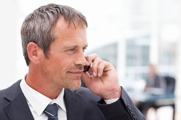 Uomo d'affari telefonando nel suo ufficio