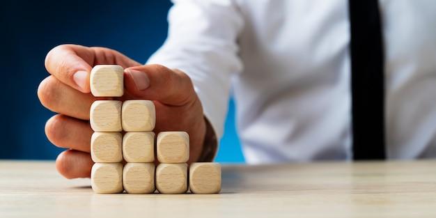 Uomo d'affari che mette i dadi di legno in bianco in una scala come la struttura in un'immagine concettuale.