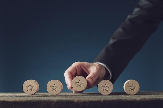Imprenditore mettendo cinque cerchi in legno tagliati con forma a stella su di essi in fila su una scrivania