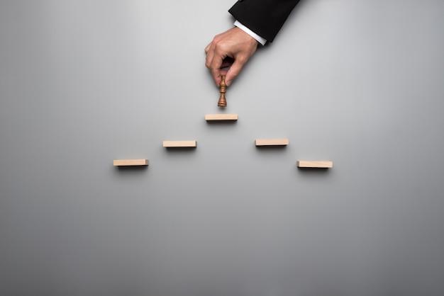 Uomo d'affari che mette un pezzo degli scacchi di re su una piramide dei blocchi di legno in un concetto di successo