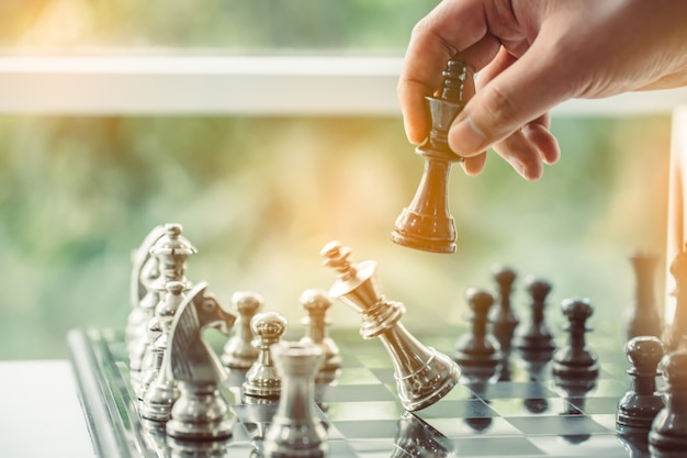 Uomo d'affari che gioca il piano di scacchi del leader aziendale di successo della strategia principale
