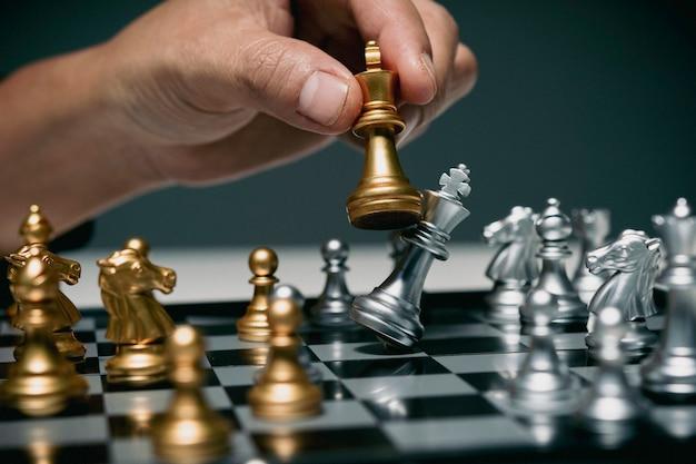 Uomo d'affari che gioca a scacchiera, concorrenza negli affari, mano di un uomo d'affari fiducioso usa il pezzo degli scacchi del re giocando per rovesciare la strategia aziendale della squadra opposta per la vittoria e il successo.