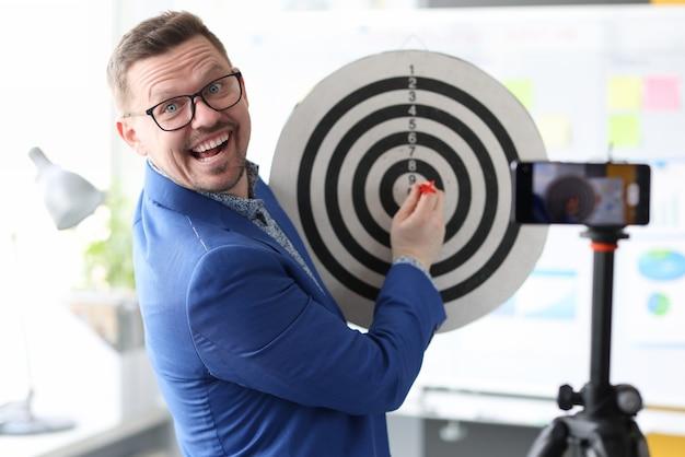 L'uomo d'affari che gioca a freccette davanti alla fotocamera del telefono cellulare fa soldi velocemente su internet