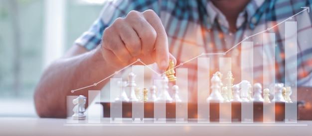 Uomo d'affari che gioca con una partita a scacchi alla ricerca di strategie per sconfiggere il concetto di analisi della strategia aziendale dei concorrenti