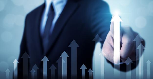 L'uomo d'affari indica il piano di crescita futura aziendale del grafico della freccia e aumenta la percentuale