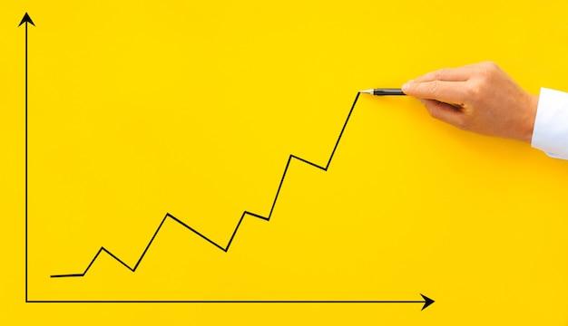 Imprenditore che punta il grafico a freccia con la penna