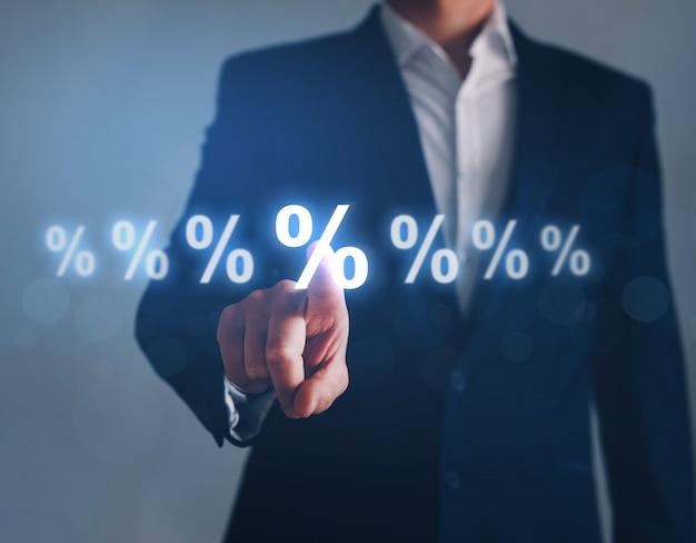 Uomo d'affari che indica il simbolo di percentuale digitale tasso di interesse finanziario e tassi ipotecari
