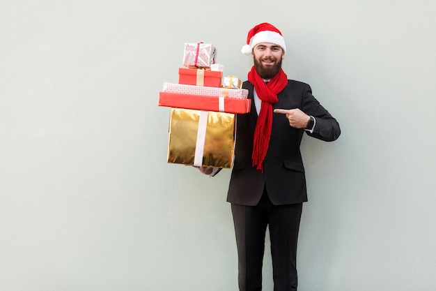 Uomo d'affari che punta il dito su molte scatole regalo colorate e guarda la macchina fotografica e sorride a trentadue denti