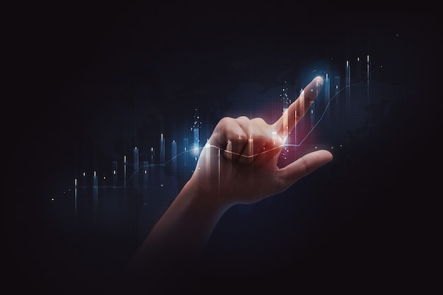 Uomo d'affari che punta il dito al grafico finanziario del mercato azionario scambia denaro o tasso di analisi dell'economia globale degli investimenti di crescita su sfondo di tecnologia economica con attività di dati commerciali digitali.