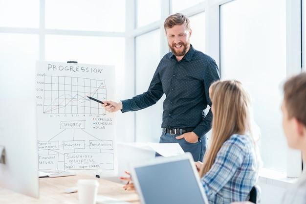 Uomo d'affari che punta al grafico durante la presentazione aziendale