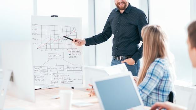 Uomo d'affari che punta al grafico durante la presentazione aziendale.