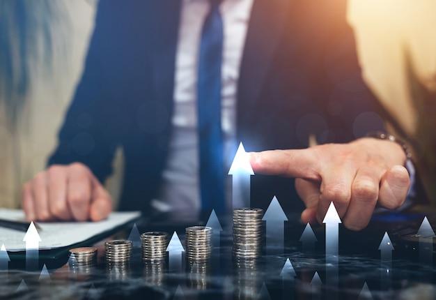 Imprenditore indicando aumentare la crescita del grafico sopra le pile di monete. sviluppo aziendale verso il successo e aumento dei profitti.