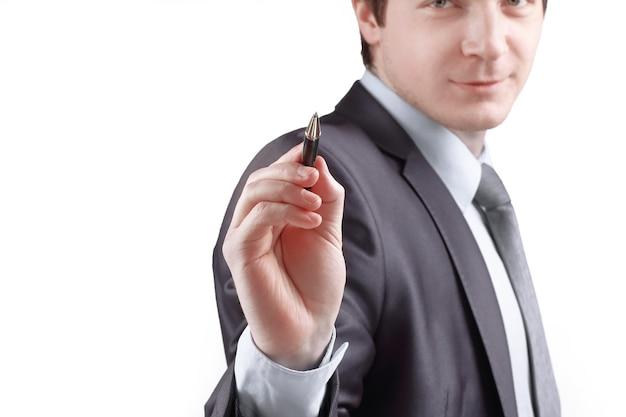 Imprenditore puntando una penna alla copia spazio isolato su sfondo grigio.