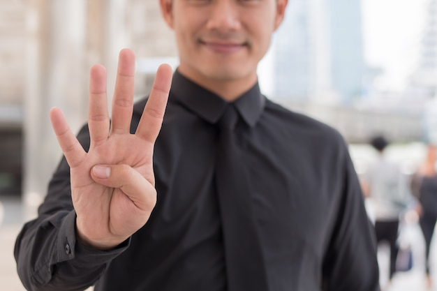 Imprenditore rivolto verso l'alto numero 4 dito gesto della mano