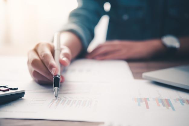 L'uomo d'affari che indica con la penna sul grafico del rapporto aziendale sta lavorando sui conti nell'analisi aziendale con grafici e documentazione.