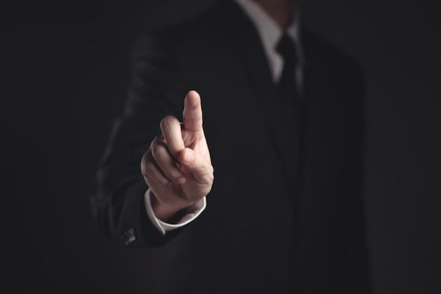 Uomo d'affari che presenta in abito nero su fondo nero