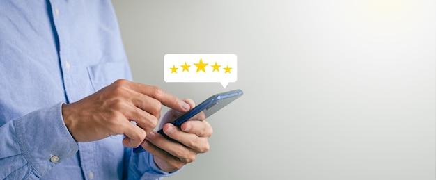 L'uomo d'affari preme il pulsante di primo piano sullo schermo dello smartphone con l'icona della stella luminosa dorata e la gradazione della stella fresca per ottenere il punteggio migliore. può essere utilizzato nel settore tecnologico