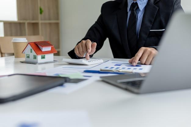 L'uomo d'affari preme una calcolatrice per calcolare l'importo su un documento di vendita di immobili residenziali, si incontra con il responsabile delle vendite per effettuare una vendita e fare promozioni, piani di marketing per aumentare le vendite