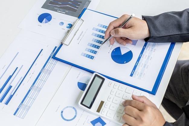 L'uomo d'affari preme una calcolatrice bianca, è il proprietario dell'azienda, sta controllando i documenti finanziari dell'azienda nel suo ufficio, i documenti finanziari mostrano il formato grafico. concetto di gestione finanziaria