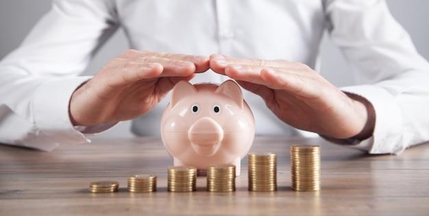 L'uomo d'affari protegge il porcellino salvadanaio e le monete. risparmiare soldi