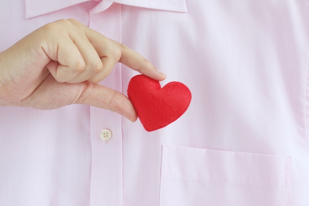 Uomo d'affari che tira fuori o in un cuore rosso dalla tasca della camicia rosa