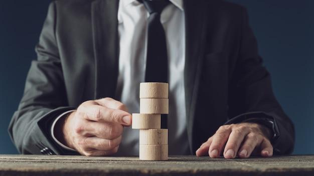 Imprenditore spingendo un cerchio di legno tagliato in una pila di loro nell'immagine concettuale della visione aziendale e della strategia.