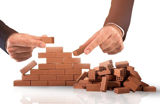 L'uomo d'affari mette un mattone per costruire un grande muro. concetto di nuovo business, partnership, integrazione e avvio