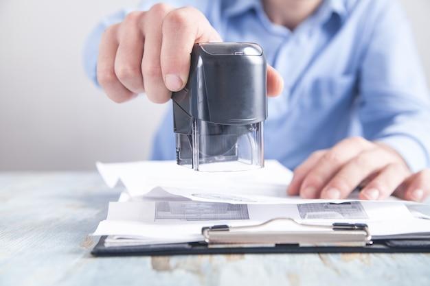 L'uomo d'affari mette un timbro sui documenti in ufficio.