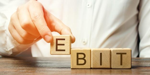L'uomo d'affari mette i blocchi di legno con la parola ebit