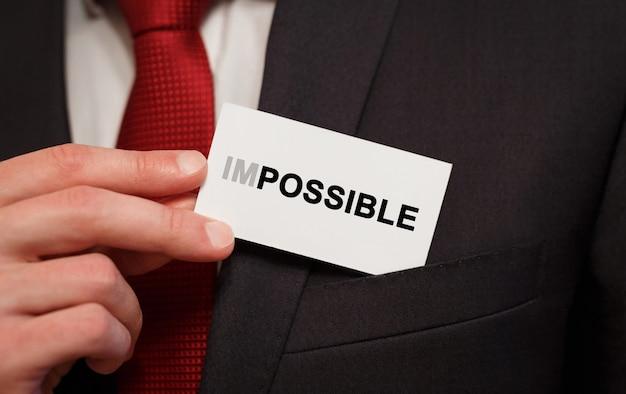 Uomo d'affari che mette una carta con testo impossibile in tasca