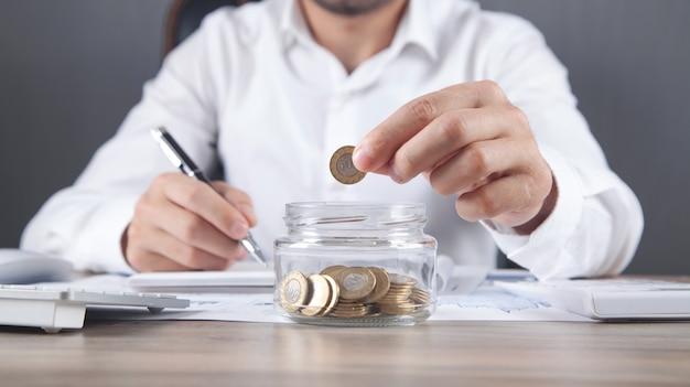 Uomo d'affari che mette moneta in banca di vetro. risparmiare soldi