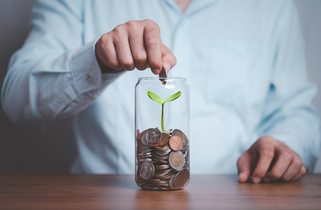 Uomo d'affari che mette moneta per risparmiare denaro vaso che ha la crescita degli alberi all'interno
