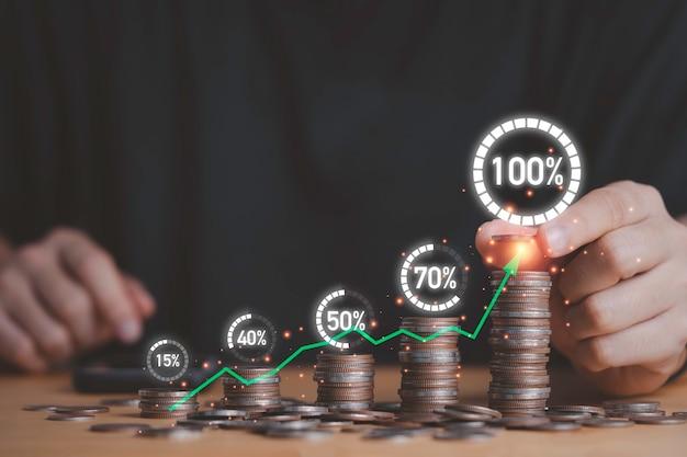 Uomo d'affari che mette la crescita di impilamento delle monete con caricamento percentuale del cerchio virtuale, risparmio di denaro di deposito e concetto di crescita del profitto aziendale