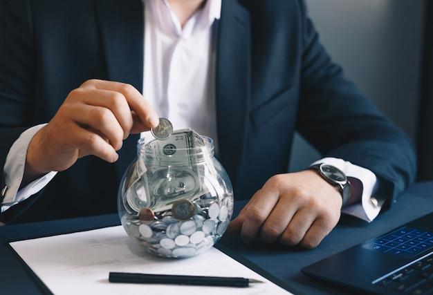 Uomo d'affari che mette le monete in un barattolo di vetro